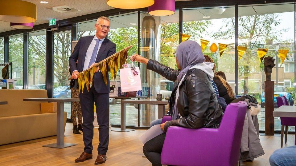 Wethouder René van Ginderen reikt coronaproof diploma's uit aan de twaalf leerlingen van TOP Academie.